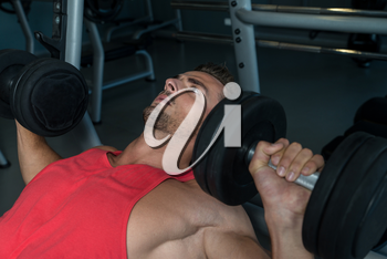 Man Lies On A Bench And Does Dumbbell Presses