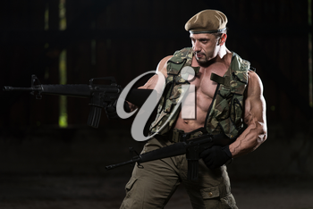 Action Hero Muscled Man Holding Machine Guns - Standing In Abandoned Building Wearing Green Pants