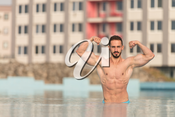 Portrait Of A Very Muscular Sexy Man In Underwear At Swimming Pool Showing Double Biceps Pose
