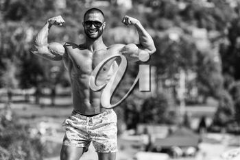 Portrait Of A Physically Fit Man Showing His Well Trained Body Outdoors In Summer Time
