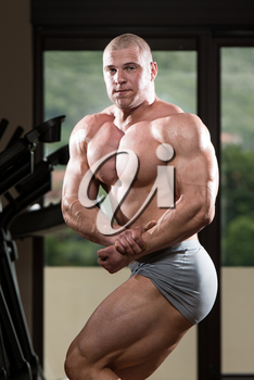 Portrait Of A Young Man Posing Bodybuilding Poses In Modern Fitness Center