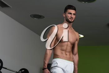 Portrait Of A Young Physically Fit Man Holding Weights And Showing His Well Trained Body
