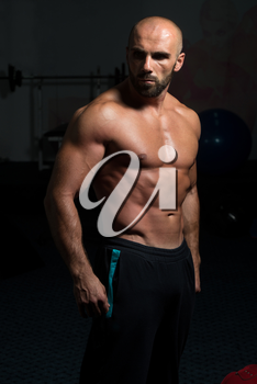Portrait Of A Physically Fit Man Showing His Well Trained Body In A Dark Room