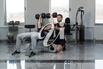 Personal Trainer Showing Young Man How To Train Chest Exercise With Dumbbells In A Health And Fitness Concept