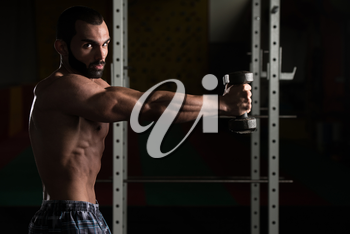 Young Man Working Out Shoulders In A Dark Gym - Bodybuilder Doing Heavy Weight Exercise For Shoulder