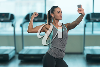 Pretty Mixed Race Woman Taking A Selfie In Fitness Center - Gym In The Background