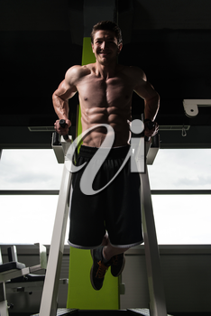 Young Muscular Fitness Bodybuilder Doing Heavy Weight Exercise For Triceps And Chest on Parallel Bars In The Gym