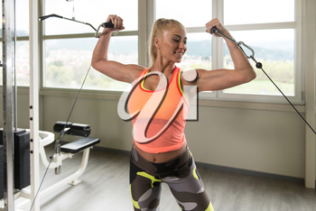 Healthy Fitness Woman Doing Heavy Weight Exercise For Biceps On Machine In The Gym