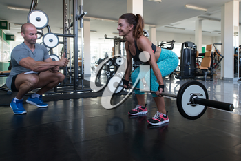 Personal Trainer Showing Young Woman How To Train Back With Barbell In The Gym