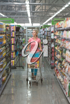 Shopping Woman Looking at the Shelves in the Supermarket - Portrait of a Young Girl in a Market Store With a Shopping Cart