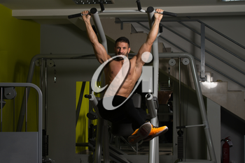 Muscular Man Performing Hanging Leg Raises Exercise - One Of The Most Effective Ab Exercises