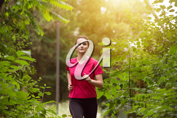 Young Woman Running In Wooded Forest Area - Training And Exercising For Trail Run Marathon Endurance - Fitness Healthy Lifestyle Concept