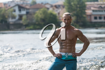Handsome Mature Man Standing Strong Outdoors In Nature And Flexing Muscles - Muscular Athletic Bodybuilder Fitness Model Posing After Exercises
