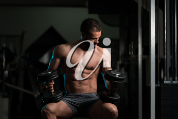 Good Looking And Attractive Young Man With Muscular Body Sitting On Bench And Relaxing In Gym