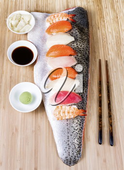 Vertical display of several pieces of assorted sushi placed on large salmon fillet with soy sauce, spicy Japanese mustard, ginger, and chop sticks on wooden bamboo board