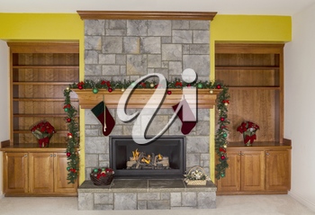 Large Natural Gas fireplace decorated for the holidays with accent yellow wall in background