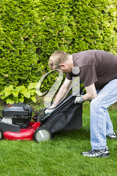 Vertical photo of a mature man, dressed in blue jeans and t-shirt, putting grass bag on old gas lawnmower with tall bushes in background