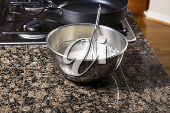 Pancake batter in stainless steel bowl with whisk and stove top in background