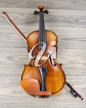Antique violin and bow on faded wooden table background