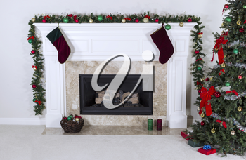 Natural Gas Fireplace decorated with tree, ornaments, stockings, basket and gifts