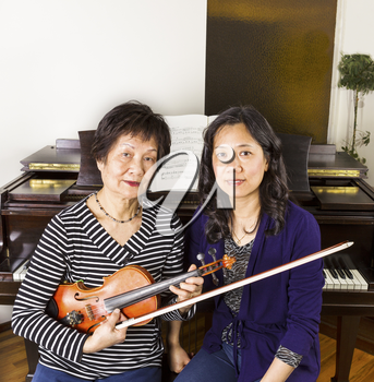 Female Violin and piano teachers sitting next to each other with piano in background