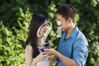 Horizontal photo of a young adult man handing his lady friend a drink while outdoors with green trees in background