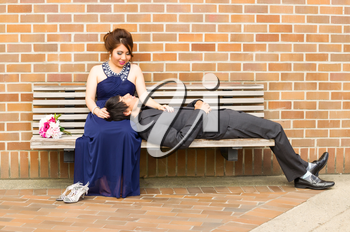Horizontal Photo of young adult woman looking at her lover as he is lying down in her lap with brick wall in background