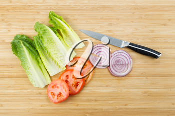 Horizontal photo of freshly cut lettuce, onion and tomato slices on natural bamboo board with kitchen knife
