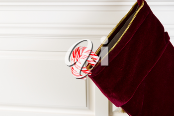 Horizontal photo of Christmas stocking hanging from fireplace mantle with real candy canes hanging outside