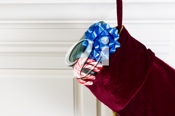 Horizontal photo of Christmas stocking hanging from fireplace mantle with real candy canes and packaged gift hanging outside