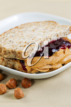 Closeup vertical photo of a peanut butter and jelly sandwich cut in half, inside white plate with whole nuts lying on textured table cloth