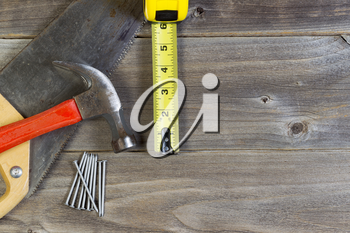 Top view of home repair tools consisting of wood saw, hammer, nails, and tape measure on rustic wooden boards