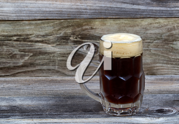 Horizontal image of a glass stein filled with dark draft stout beer on rustic wood