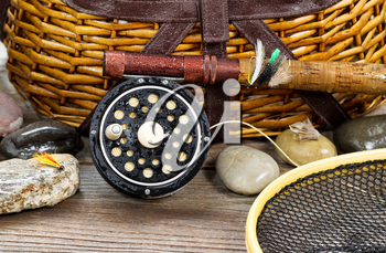 Close up of a wet antique fly fishing reel, rod, landing net, artificial flies and rocks in front of creel with rustic wood underneath. Layout in horizontal format.