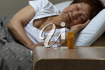 Close up of an open bottle of medicine and a glass of water on nightstand with senior woman sleeping in background. Sickness concept.
