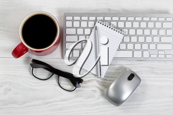 White desktop with red coffee cup, partial keyboard, mouse, reading glasses, paper and pen.
