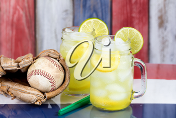 Close up of a glasses filled with cold lemonade with baseball glove and ball.  Faded wooden boards painted red, white and blue in background. Selective focus on upper front jar glass with lime slice.