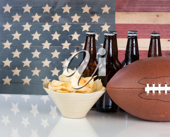 Football, potato chips, cold beer in bottles on white glass table with United States flag painted on rustic wood. Layout in horizontal format with copy space.