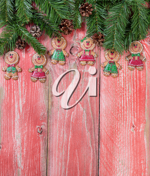 Christmas holiday gingerbread cookies and evergreen branches on rustic red wood. Vertical format.