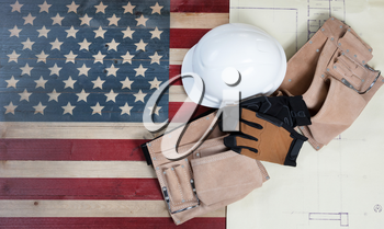 Labor Day background with USA rustic wooden flag, drawing blue prints and used industrial tools plus utility belt