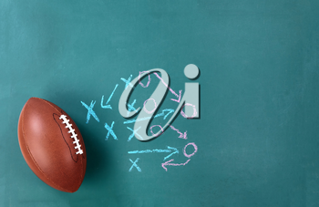 American football with game plan on cleaned chalkboard