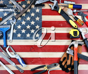 Labor Day concept with circle border of industrial worker tools over distressed United States wooden flag background