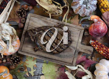 Freshly grilled steak with seasonal autumn decorations on table