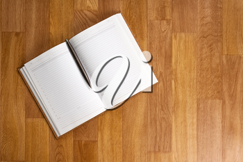 Blank notepad with office supplies on wooden table. Above view.