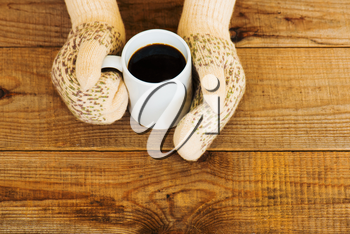 Woman hands in teal gloves are holding a mug with hot coffee or cocoa.  Winter and Christmas concept.