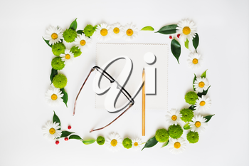 Paper, pencil and glasses with wreath frame from chamomile and chrysanthemum flowers, ficus leaves and ripe rowan on white background. Overhead view. Flat lay.