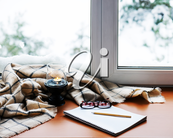 Open notepad, glasses, candle, pencil and beige warm plaid located on stylized wooden windowsill. Winter concept of comfort and relaxation.