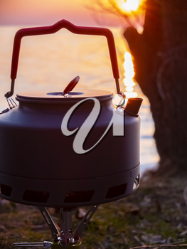 Boiling water in a touristic kettle outdoors next to the water at sunset.