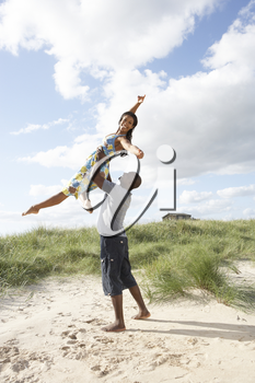 Energetic Young Couple Having Fun In Dunes By Beach