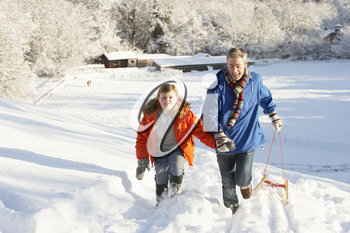 Father And Son Pulling Sledge Up Snowy Hill